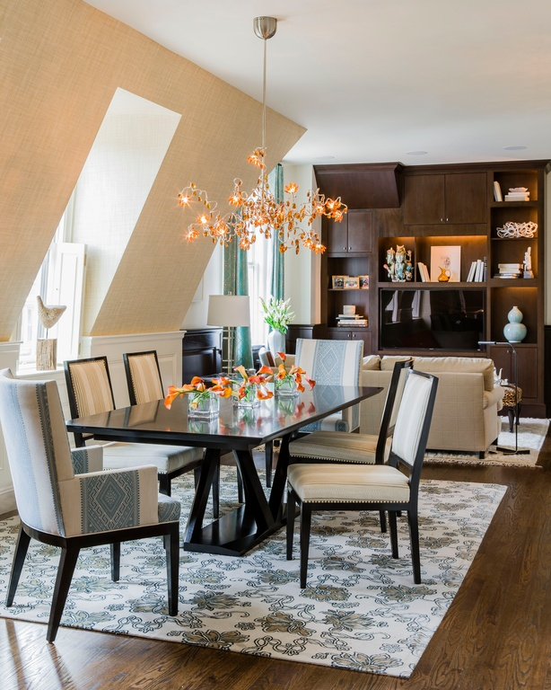 Contemporary dining room with detailed, cushioned dining chairs. A black dining table sits on an area rug