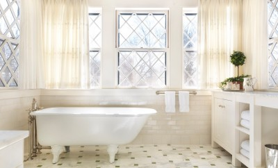 Traditional master bathroom with white, free-standing tub. White vanity and tiled floors.
