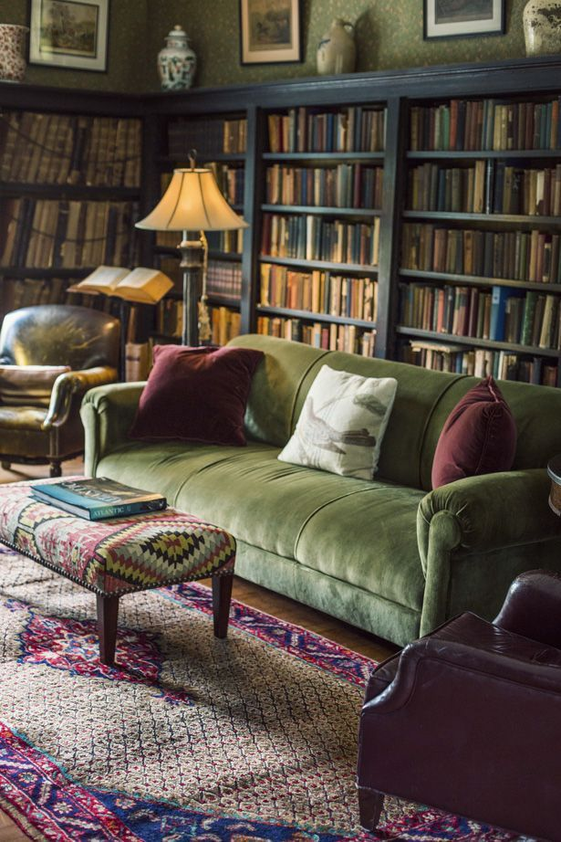 Lived in library with plush green sofa, leather side chairs, green wallpaper, bookshelves, patterned ottoman and rug.