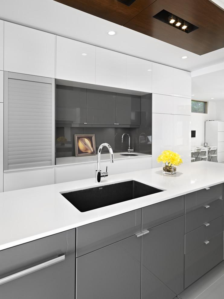 modern kitchen in Edmonton with flat-panel cabinets, gray cabinets, gray backsplash and glass sheet backsplash.