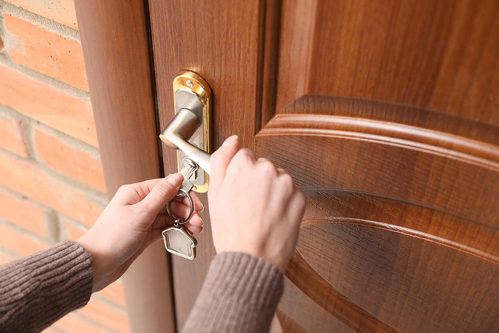 Woman With Key Opening Front Door, Closeup